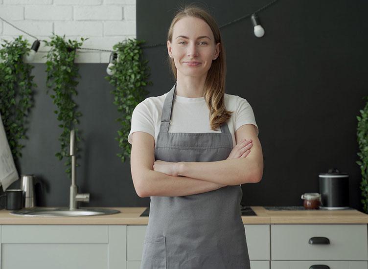 Jeune femme portant un tablier gris souriante et croisant les bras debout dans sa cuisine