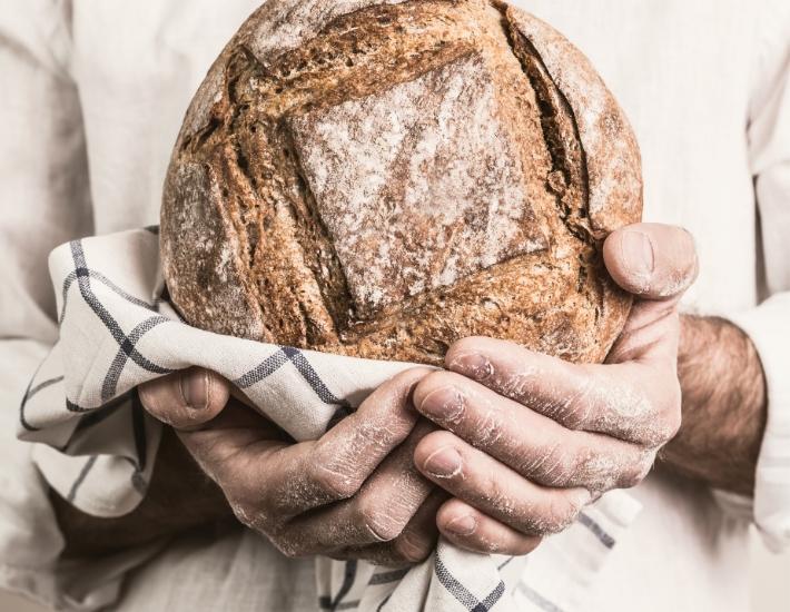 Boulanger tenant un pain dans ses mains