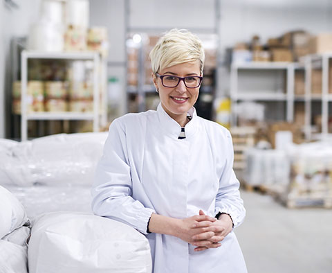 Femme accoudée à un sac de farine en entrepôt